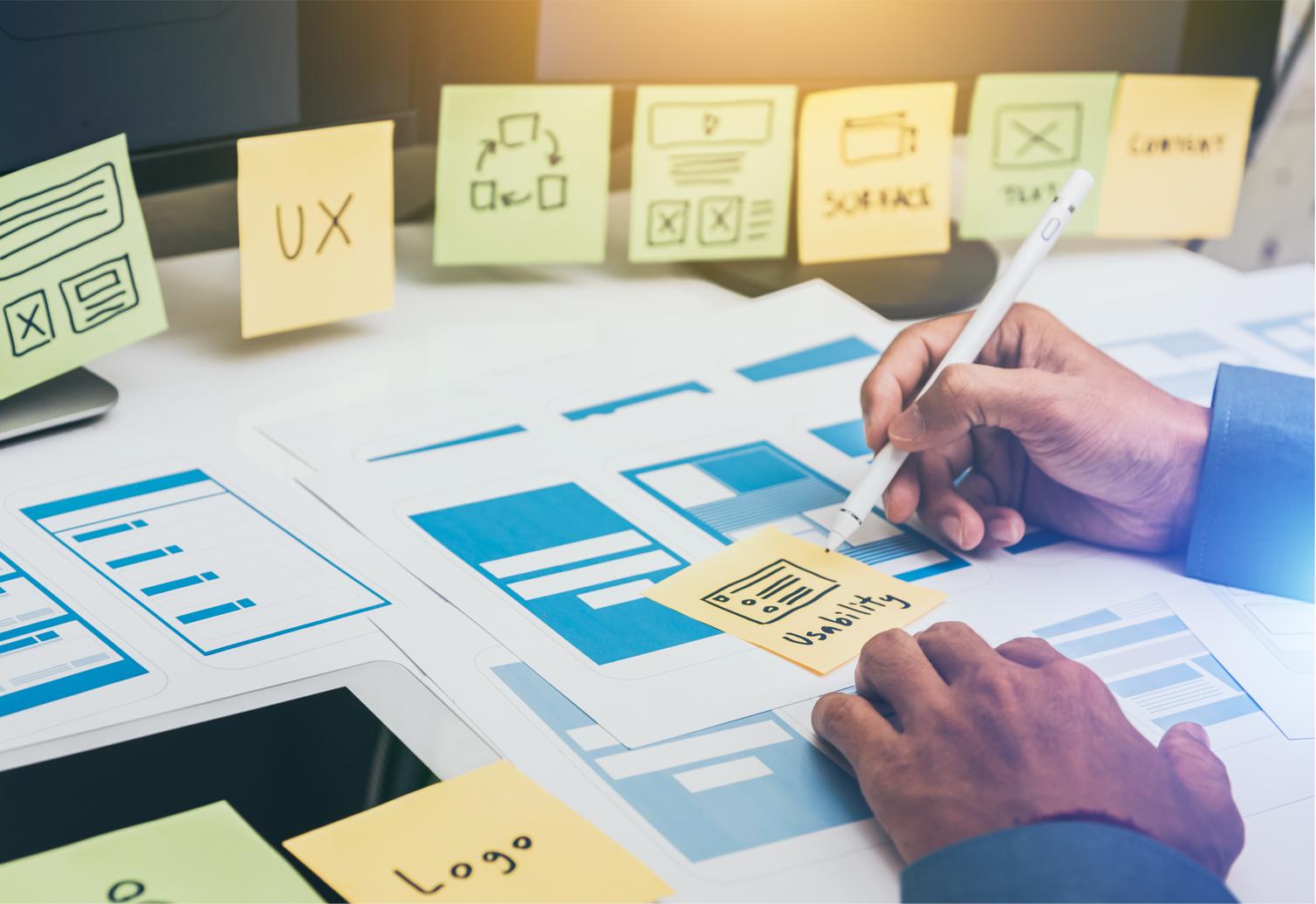 Pessoa realizando o trabalho e a cultura de UX com wireframe e post it