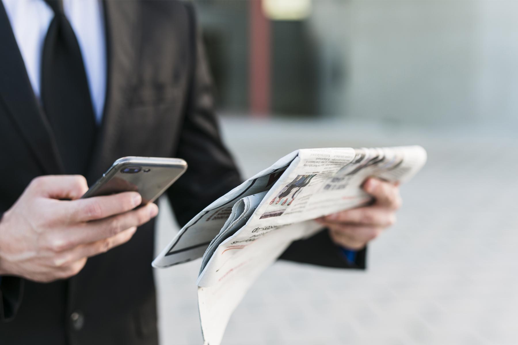 Homem segurando o jornal em papel e o celular